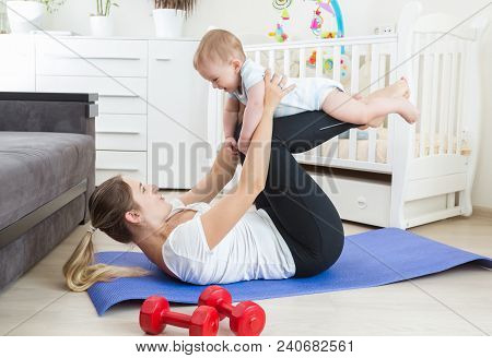 Beautiful Smiling Baby Practising Fitness With Young Mother On Floor At Home
