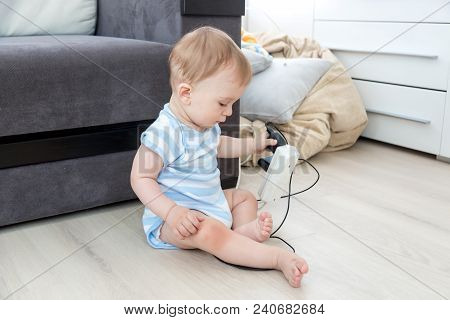 Unattended Baby Sitting On Floor And Playing With Electric Cables. Concept Of Baby In Danger
