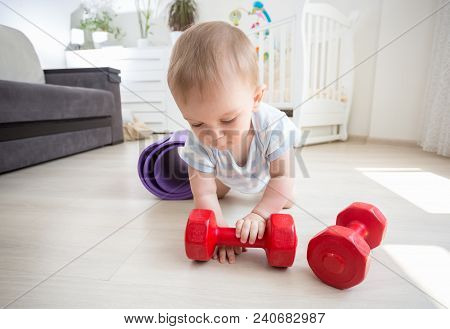 Portrait Of Baby Boy Palying With Red Dumbbells On Floor At Home