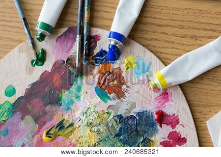 fine art, creativity, painting and artistic tools concept - close up of acrylic color or paint tubes, palette and brushes