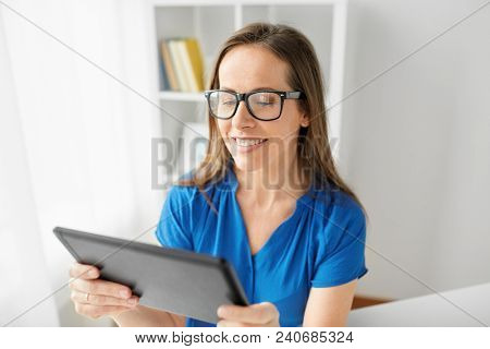 business, people and technology concept - happy smiling middle-aged woman in glasses with tablet pc computer working at home or office