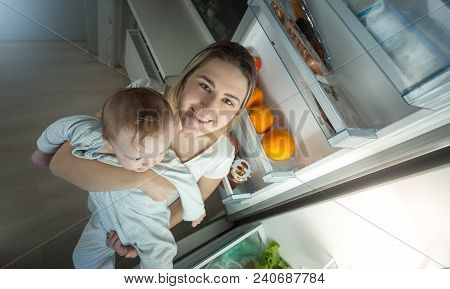 Portrait Of Mother Holding Her Baby Boy And Standing At Open Refrigerator On Kitchen At Night