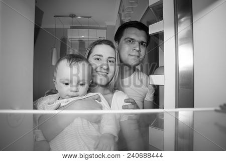 Black And White Portrait Of Family Feeling Hungry At Night Looking Inside The Refrigerator
