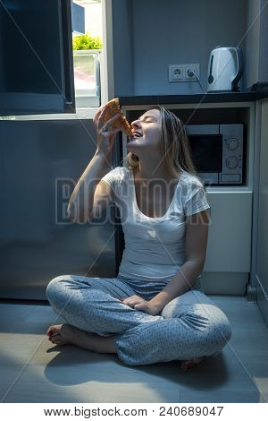 Portrait Of Hungry Woman Enjoying Eating High Calorie Pizza On Kitchen At Night