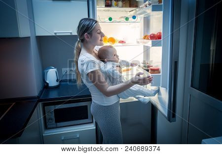 Young Mother Taking Food Out Of Refrigerator At Night To Cook Something For Her Hungry Baby Boy