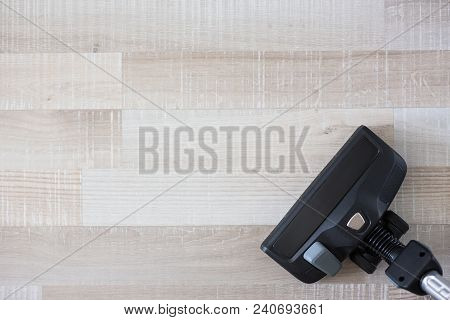 Top View Of Vacuum Cleaner Over Wooden Floor Background