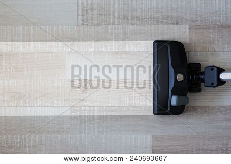 Housekeeping Before And After Concept - Vacuum Cleaner Over Wooden Parquet Floor Background