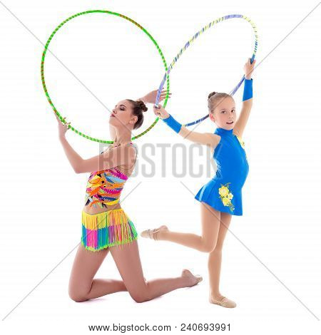 Beautiful Sporty Woman And Little Girl Gymnasts Doing Exercises With Hoops Isolated On White Backgro