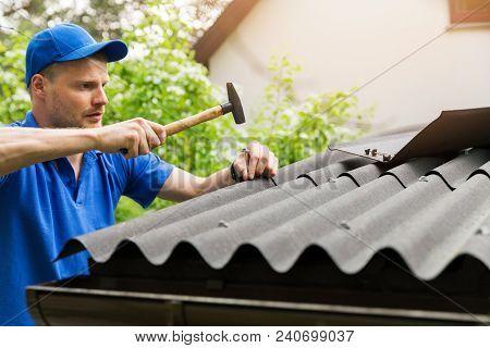 Roofer In Blue Uniform Installing Bitumen Roof Sheets