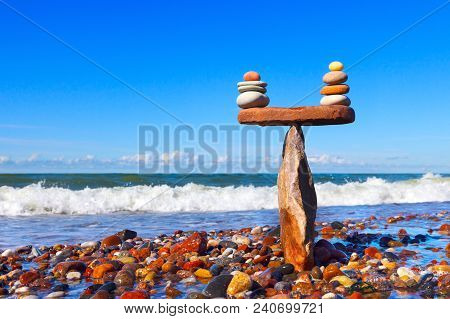 Symbolic Scales Of Stones Against The Background Of The Sea And Blue Sky. Concept Of Harmony And Bal