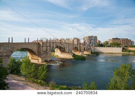 a view of the ancient Stone Bridge, or Puente de Piedra in Spanish, over the Ebro River in Zaragoza, Spain