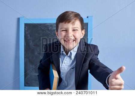Cheerful Clever Schoolboy In Uniform With Book In A Classroom.  He Is Happy To Start Learning.