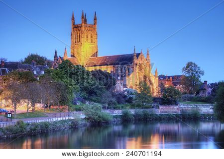 Worcester Cathedral Floodlit On A Spring Evening And Reflected In The River Severn.
