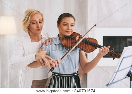 Need Your Advice. Cheerful Young Female Person Holding Violin While Playing Classical Melody