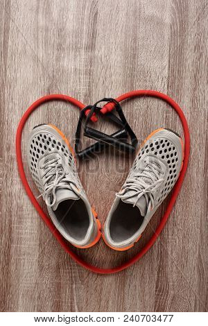 Heart Shaped Gym Shoes And Expander On Wooden Background