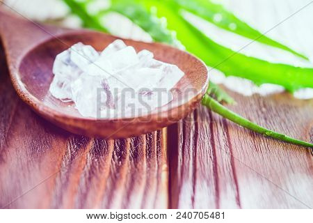Aloe Vera Gel And Rock Salt On Wooden Background. Spa And Skin Care Concept. Closeup Aloe Vera Leaf.