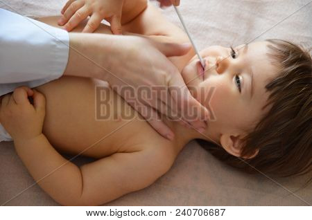 Pediatrician Examining Throat Of A Little Ill Girl. Kid Looks Sick And Sad. Doctor Visit His Patient