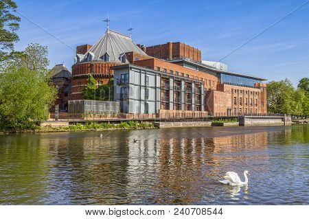 The Royal Shakespeare Theatre, home of the Royal Shakespeare Company, reflecting in the River Avon, with a swan in the foreground. poster