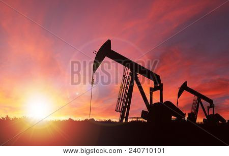 Pumpjack Silhouette Against A Sunset Sky With Deliberate Lens Flare And Copy Space. These Jacks Can
