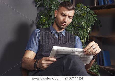 Handsome Stylish Man Sits In Chair And Reads Latest News In Newspaper. Confident Brutal Businessman
