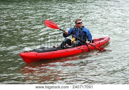 Falmouth, Cornwall, Uk - April 12 2018: Man Wearing Blue Wetsuit And Sunglasses Paddling A Kayak On