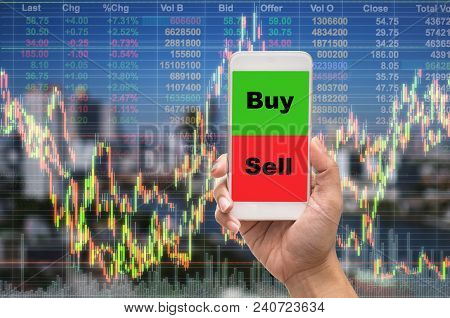 Female Hand Holding Mobile Phone Touch Screen Showing Buy And Sell Over The Stock Market Exchange In