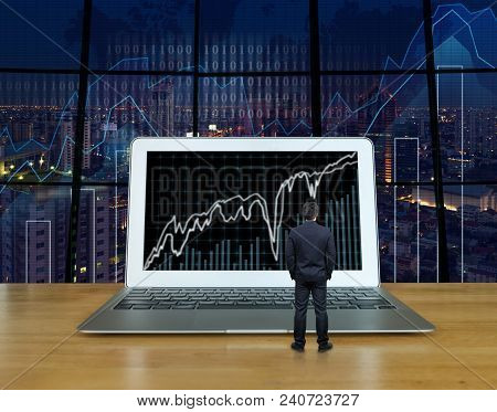 Businessman Standing On The Wood Table Which Have The Computer Laptop Showing The Trading Graph At T