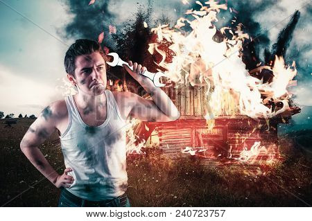 Angry Man Holding A Wrench With His House On Fire In The Background. Home Insurance Concept.