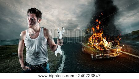 Man Holding A Wrench With His Car On Fire In The Background. Needs Help To Repair The Car. Car Insur