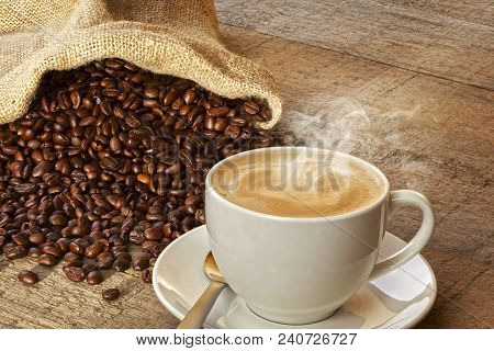 Coffee And Sack Of Coffee Beans - A Cup Of Hot Steaming Coffee On A Rustic Plank Background, With A