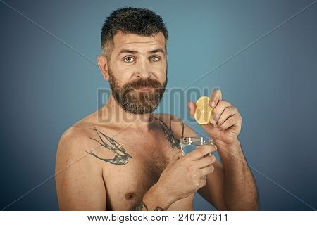 Man With Long Beard Hold Water Glass On Blue Background. Hipster Drink Clean Healthy Water With Lemo