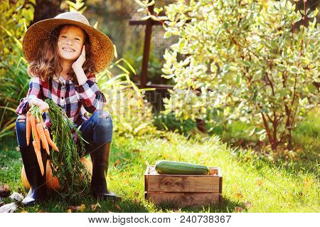 Happy Farmer Child Girl Sitting With Autumn Harvest In The Garden. Growing Fresh Organic Vegetables,