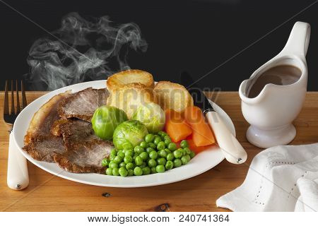 Roast Beef Concept - Steaming Hot Roast Beef With Roast Potatoes, Brussels Sprouts, Carrots, Peas An