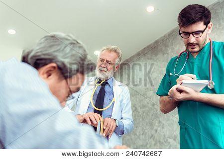 Portrait Of Doctor Team Are Examining  Symptom Of Senior Patient In Examination Room., Healthcare An