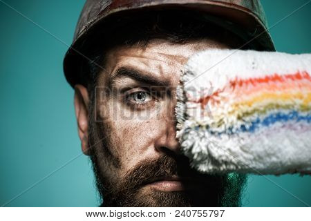 Painter With Painting Roller. Professional Painter Worker In Protective Helmet. Bearded Decorator Ho