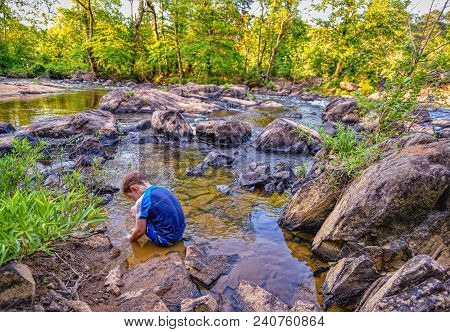 A little boy is crouching down playing in a shallow pool of water by the shore of a rocky river. High definition.