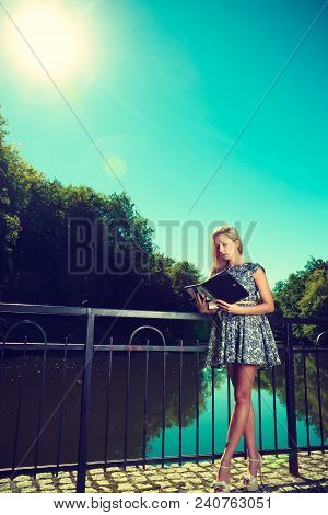 Technology, Outdoor Relaxation Concept. Woman In Park, Relaxing And Using Tablet Near River, Ebook S