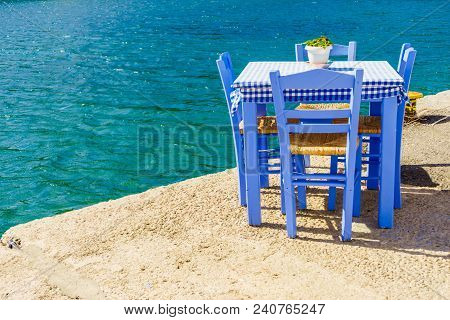 Seaside Blue Table And Chairs Open Cafe Outdoor Restaurant In Greece On Sea Shore. Summer Vacation O