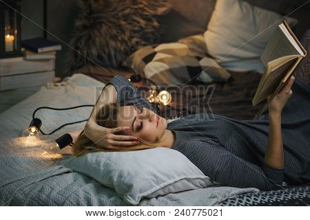 Young Attractive Girl Is Reading A Book In Her Bedroom. She Lies On A Pillow In Her Bed And Holds A