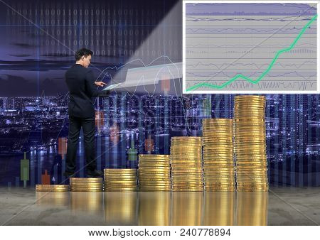 Asian Businessman Standing Over The Stack Of Gold Coins And Using The Tablet Present The Trading Gra