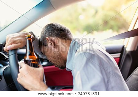 Drunk Asian Young Man Drives A Car With A Bottle Of Beer With Sunset Background, Dangerous Driving C