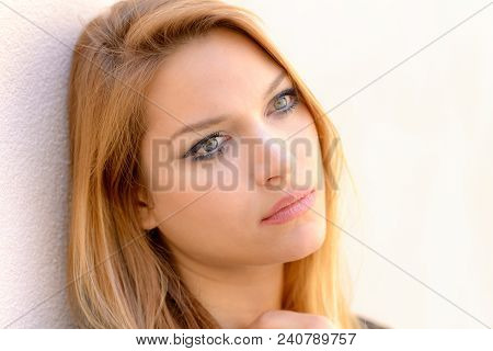 Attractive Calm Woman Looking Quietly As She Leans Against A Wall With Her Hand To Her Throat