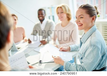 Profile view of cheerful young designer wearing denim shirt looking at her colleague with charming smile while participating in project discussion at modern boardroom