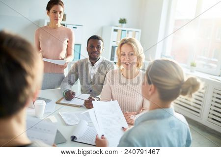 Back view of young manager wearing denim shirt sitting at boardroom table and giving speech concerning results of accomplished work while her colleagues listening to her with concentration