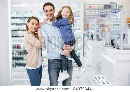 Need Medication. Confident Loving Family Coming In Drugstore And Looking At Camera