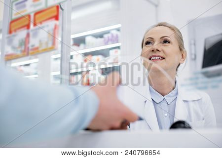 Your Order. Low Angle Of Happy Female Pharmacist Smiling And Talking With Man