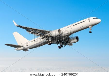 Airplane Ready For Landing Flying In The Blue Sky With Landing Gear And Flaps