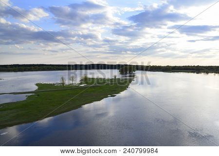 Photo Of The Spilling On The River In Spring, Green Meadow And Bright Blue Sky With Small Clouds
