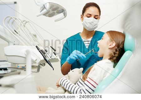 Serious concentrated young female dentist in mask and gloves examining childrens teeth in dental room, redhead girl with toy keeping mouth open at checkup