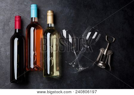 Red, rose and white wine bottles with wine glasses and corkscrew on stone table. Top view